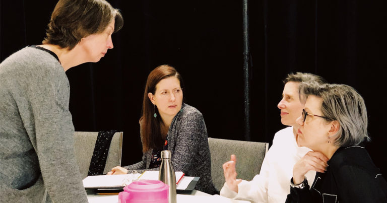 Image of four woman artists discussing play development around a table